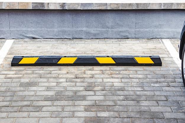 Een lege parkeerplaats in een woonwijk met gele parkeerstops voor auto's. detailopname. stop parkeerbegrenzer.