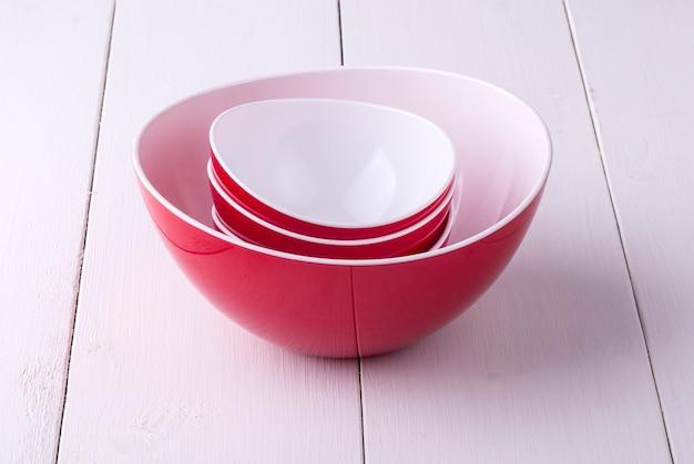 Een lege rode slakom en drie kopjes op een witte houten tafel
