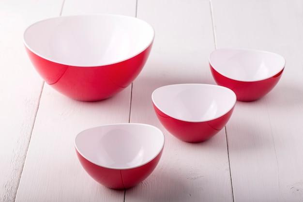 Een lege rode slakom en kopjes op een witte houten tafel