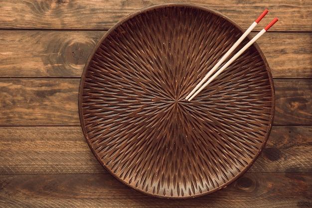 Een lege ronde plaat met twee houten eetstokjes over de tafel