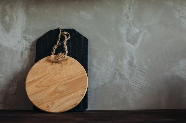 Een lege snijplank op de keuken op houten tafel tegen de grijze muur