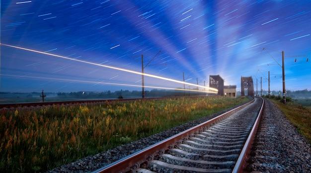 Een lege spoorlijn bij zonsopgang, een lichtspoor van een passagierstrein, opgenomen met lange sluitertijden. concept, reizen en vervoer.