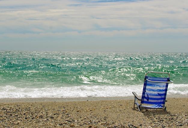 Een lege stoel op wit zandstrand in de buurt van de zee