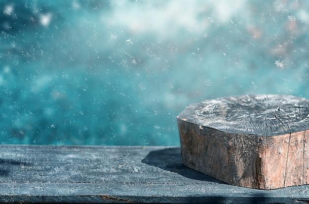 Een lege verbrande houten tafel met een stronk in de winter met sneeuwvlokken