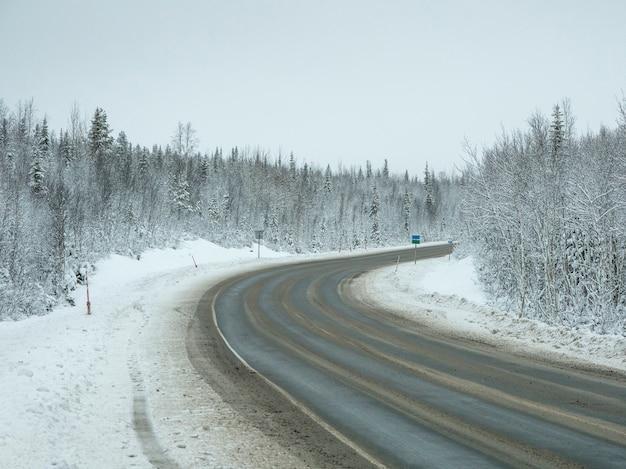 Een lege, vuile winterse snelweg. een bocht naar rechts op een gladde winterweg.