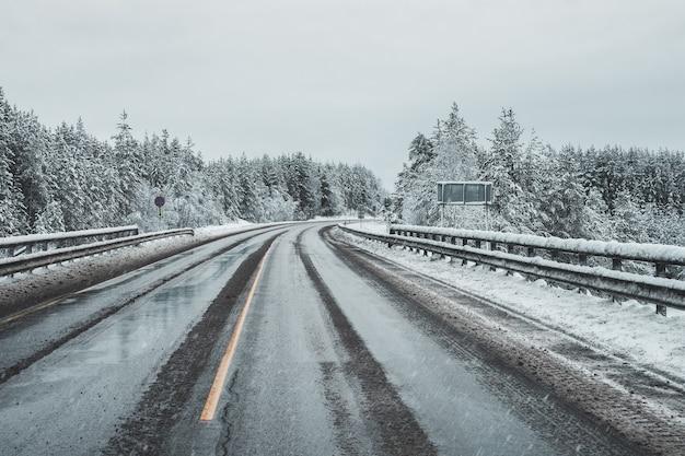 Een lege, vuile winterse snelweg. een bocht op een gladde weg.