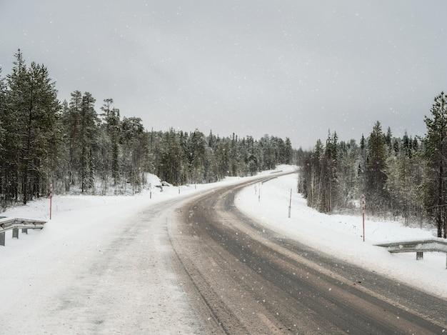 Een lege, vuile winterweg. een bocht naar rechts op een gladde winterweg.