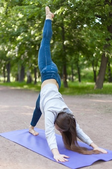 Een-legged-down-hond yoga poseert in het park steegje