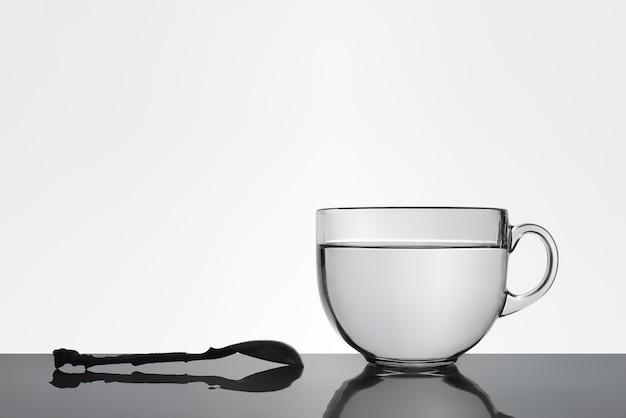 Een lepel en een kopje water op het reflecterende oppervlak