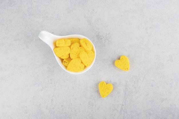 Een lepel gele koekjes op het blauwe oppervlak