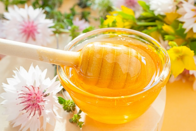 Een lepel voor honing met honing close-up, hieronder - een druppel. in de ruimte staan wilde bloemen. concept van bloemhoning, organische natuurlijke gezonde voeding.