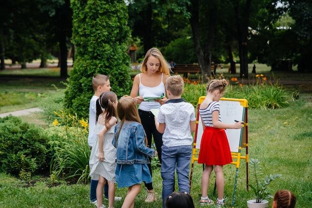 Een leraar geeft les aan een klas kinderen in een openluchtpark. terug naar school, leren tijdens de pandemie.