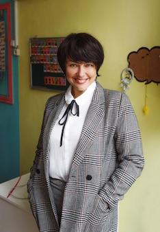 Een lerares in een grijs jasje staat in de klas