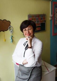 Een lerares in een witte blouse en bril staat in de klas