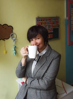 Een lerares staat in de klas en drinkt thee