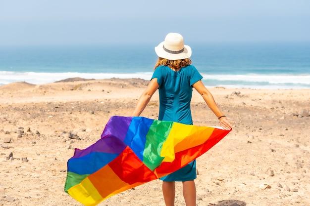 Een lesbisch persoon met een groene jurk, een witte hoed en met de lgbt-vlag bij de zee, een symbool van homoseksualiteit