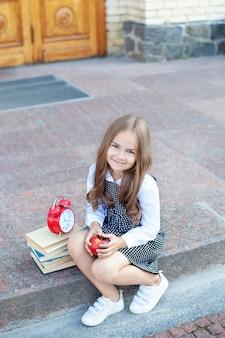 Een leuk glimlachend schoolmeisje zit op trappen van school met lunch, boeken en een wekker. terug naar school. onderwijs concept. voorschoolse educatie. kopieer ruimte. meisje studeert op buiten in de buurt van school