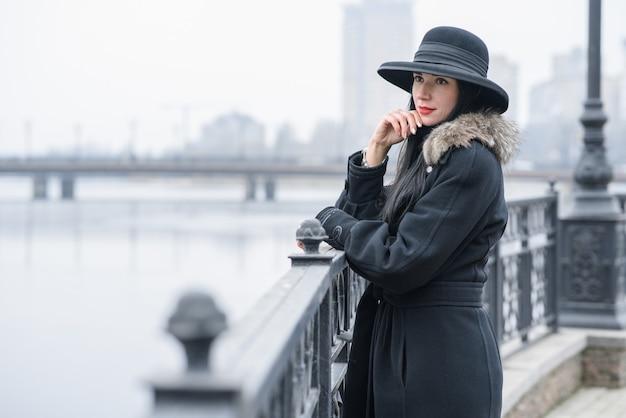 Een leuk meisje in een mooie grijze jas en hoed loopt in het park op een koude herfst
