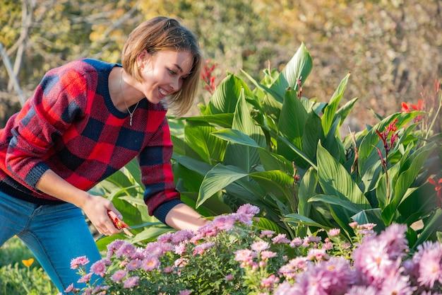 Een leuk meisje met een snoeischaar in haar handen zorgt voor bloemen in de voortuin