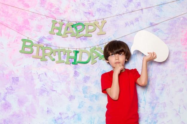 Een leuk vooraanzicht weinig jongen die in rode t-shirt wit teken houdt