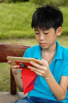 Een leuke aandacht van de aziëjongen aan het spelen van tablet in vrije tijd.