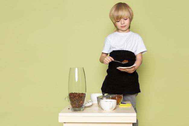 Een leuke blonde jongen die van het vooraanzicht in witte t-shirt koffie voorbereidt dichtbij lijst aangaande de steen gekleurde vloer
