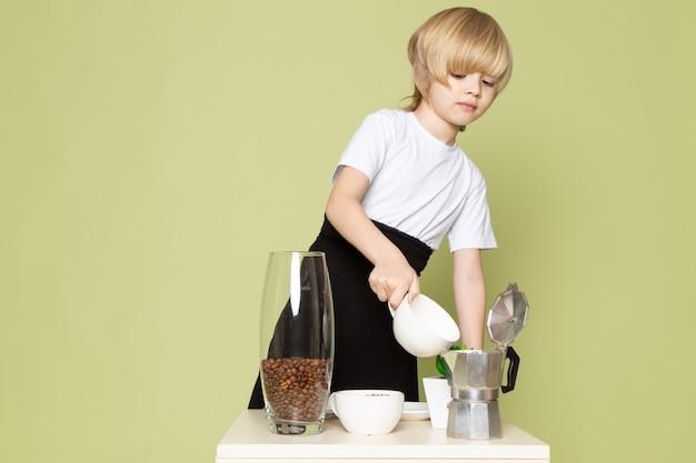 Een leuke blonde jongen die van het vooraanzicht in witte t-shirt koffiedrank op de lijst aangaande de steen gekleurde ruimte voorbereidt