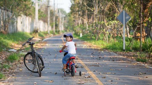 Een leuke jongen die een fiets berijdt dichtbij de grote fiets van zijn vader.
