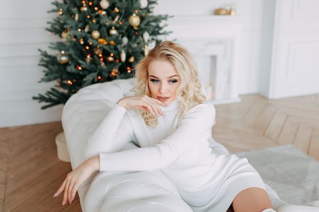 Een leuke mooie gelukkige jonge vrouw in een gebreide jurk in de buurt van een kerstboom in een licht interieur van een gezellig huis