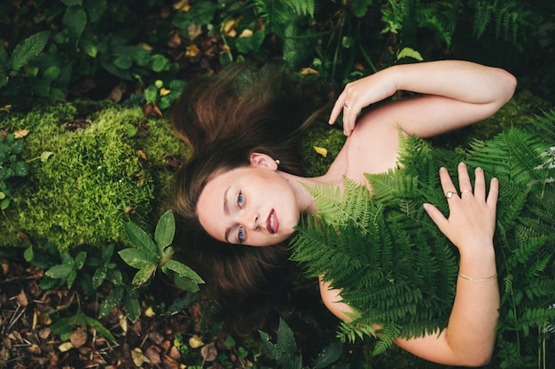 Een leuke vrouw in een bloemenjurk zit met een varenboeket in het bos.