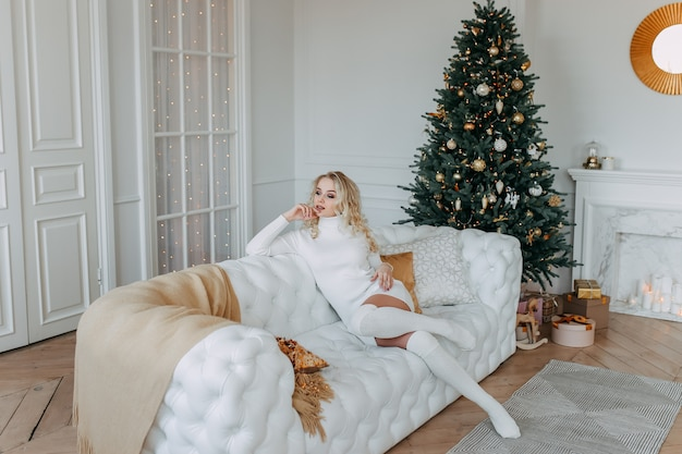 Een leuke vrouw in een jurk rust zittend op een witte bank in de buurt van een kerstboom in een licht interieur van een gezellig huis