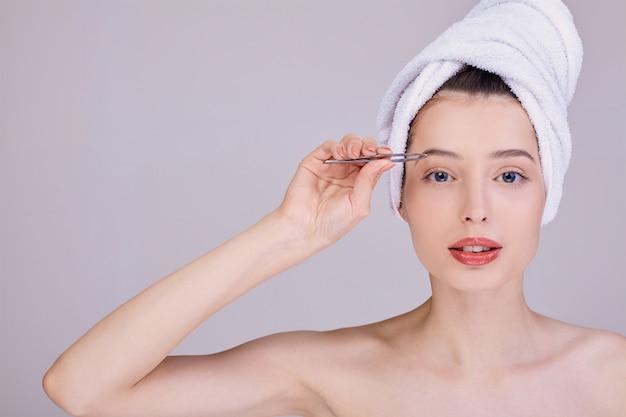 Een leuke vrouw na een douche trekt haar wenkbrauwen met een pincet.
