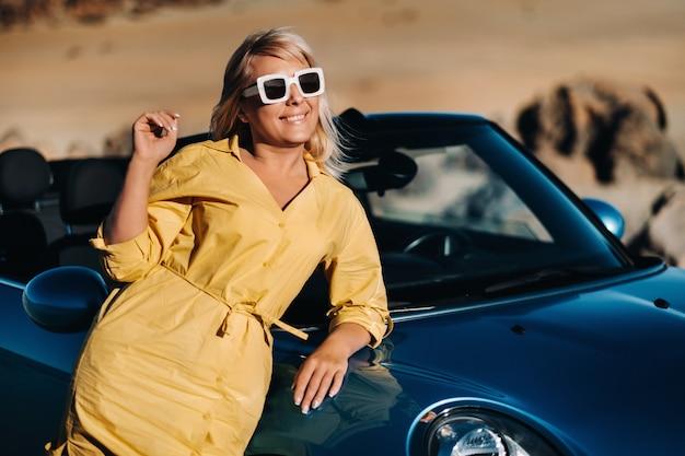 Een levenportret van een jonge vrouw die geniet van een rit door een verlaten vallei en uit een cabriolet stapt aan de kant van de weg