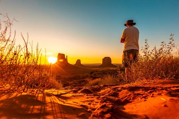 Een levensstijljongen met een hoed bij dageraad in monument valley, utah