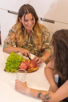 Een lgbt-paar meisjes die een salade bereiden in de keuken, een lesbisch meisjespaar, een levensstijl voor meisjesrelaties