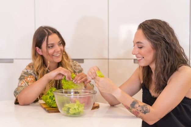 Een lgbt-paar meisjes die een salade in de keuken bereiden, een lesbisch meisjespaar thuis, een levensstijl voor meisjesrelaties