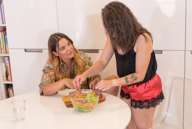 Een lgbt-paar meisjes die een salade in de keuken bereiden, lesbisch meisjespaar in hun dagelijkse thuis, meisjesrelatie-levensstijl