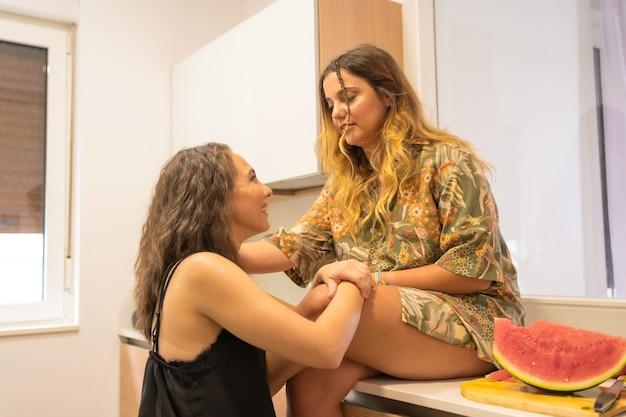 Een lgbt-paar meisjes die genegenheid tonen in de keuken thuis, lesbisch meisjespaar, levensstijl voor meisjesrelaties
