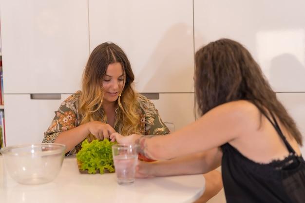 Een lgbt-paar meisjes die thuis een salade in de keuken bereiden, een lesbisch meisjespaar, een levensstijl voor meisjesrelaties