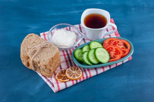 Een licht ontbijt een kopje thee, een kom met gesneden komkommer en tomaten en brood op theedoek op blauw.