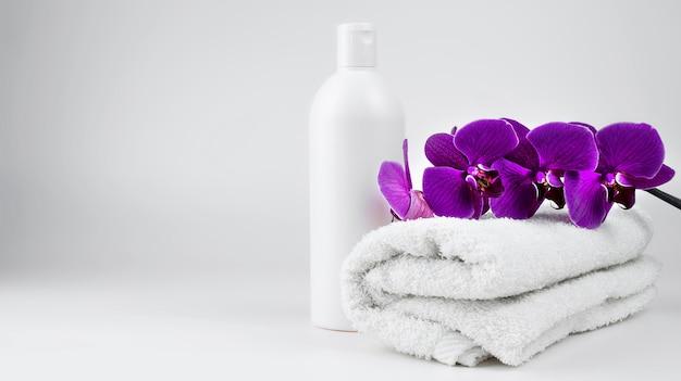 Een licht opgerolde handdoek en een wit potje crèmekleurige zeep. paarse orchideetak op een handdoek.