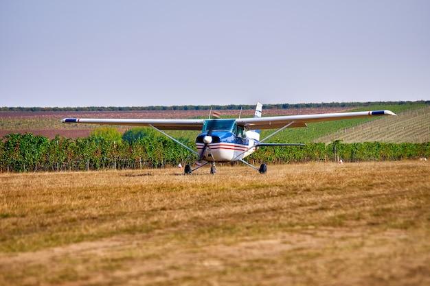 Een licht vliegtuig landt in een veld bij een wijngaard. zonnige zomerdag, mensen kijken en planten.
