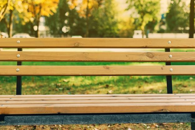 Een lichtbruine houten bank in park