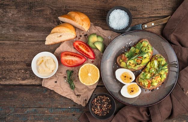 Een lichte lunch van sandwiches met avocado en tomaat met rozemarijn op houten achtergrond. bovenaanzicht met kopie ruimte. het concept van gezonde voeding.