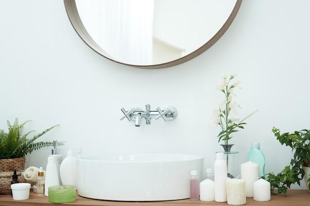 Een lichtgekleurde wasbak met spiegel en kraan naast de tubes crèmekleurige huidverzorgingscosmetica en gezichtsserums