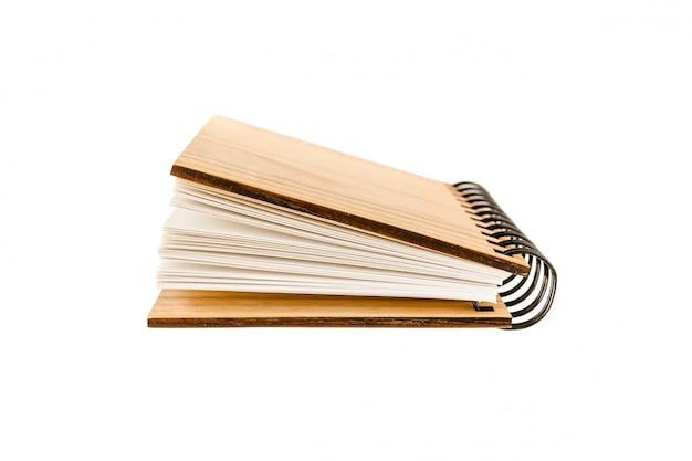 Een lichtjes open spiraalvormig notitieboek met een harde houten kaft ligt op wit