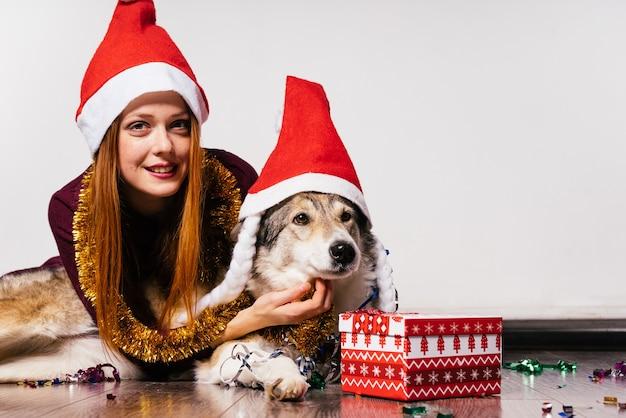 Een lief roodharig meisje met een rode muts en met een gouden klatergoud om haar nek loopt op de vloer met haar hond, wachtend op het nieuwe jaar 2018