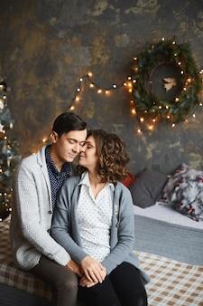 Een lief volwassen stel knuffelt en zit samen in een versierd kerstinterieur