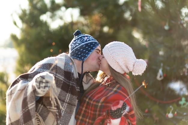 Een liefdevol koppel in warme plaids kussen met sterretjes in hun handen. maak kennis met de wintervakantie in een besneeuwd bos
