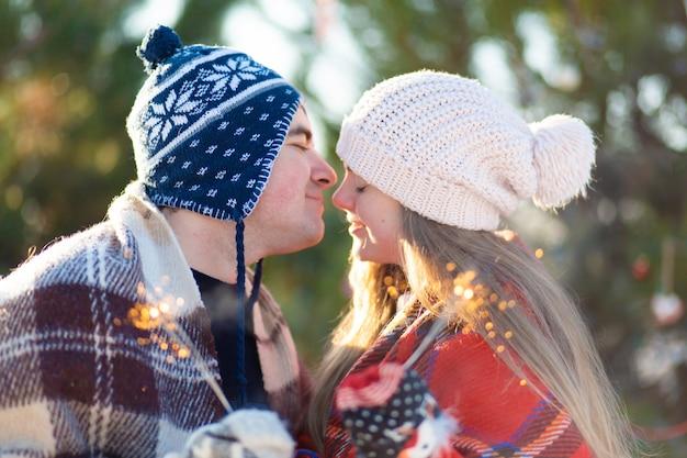 Een liefdevol koppel in warme plaids kussen met sterretjes in hun handen.